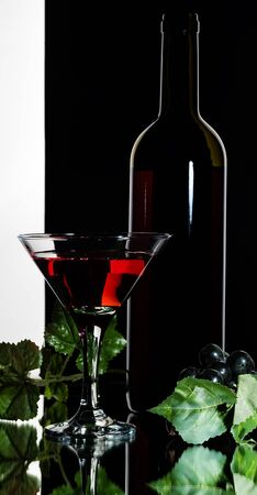 A glass of red grape wine, a bottle and a bunch of grapes on a black background.