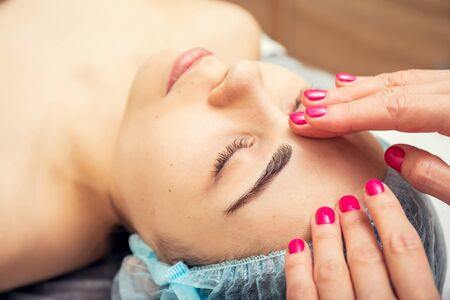 Beautiful young woman getting a facial massage with her eyes closed at the Spa. Various services in the beauty salon.