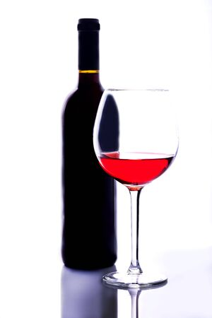 A thin-stemmed glass of red wine and a bottle of wine.
