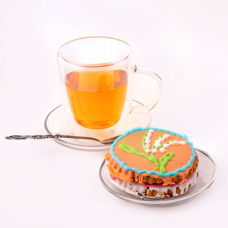 Glass Cup of black tea and a beautiful gingerbread on a white background. The concept of a delicious Breakfast. Фото со стока