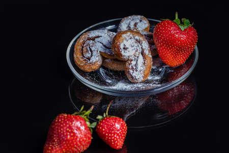 Delicious heart shaped cookies with strawberry berries on a black background. Delicious and healthy dessert.