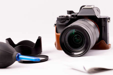 camera with lens and a pear for optics care on a white background.