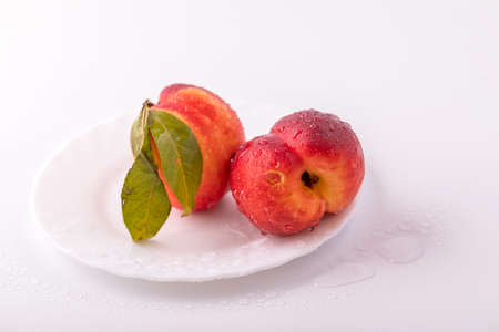 On the table nectarin peach on a white plate with water drops. Healthy and healthy food.