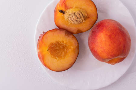 On the table nectarin peach on a white plate with water drops. Healthy and healthy food. Reklamní fotografie
