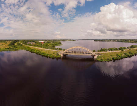 Panorama of the bridge over the Volga river in Kalyazin, Tver region, Russia. Beautiful sky, the reflection of the clouds. Photo from a drone on a Sunny day.
