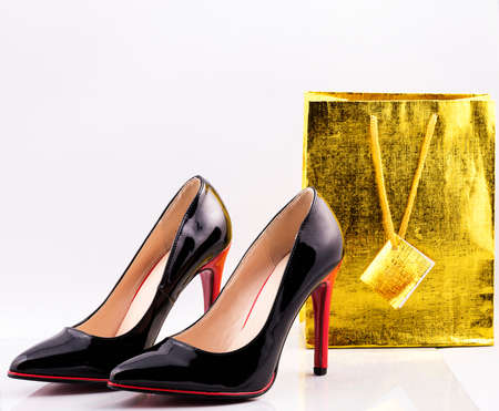 Beautiful patent leather shoes for an elegant woman with high heels on a white table.