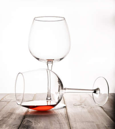 Two glasses on a thin stem on a white background, in one the remains of red wine. Reflection.A thin-stemmed glass with red wine and a cherry on the edge. 写真素材