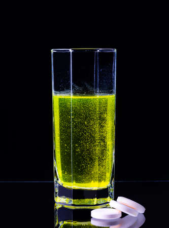 A large tablet dissolves in a glass of water on a black background. Imagens