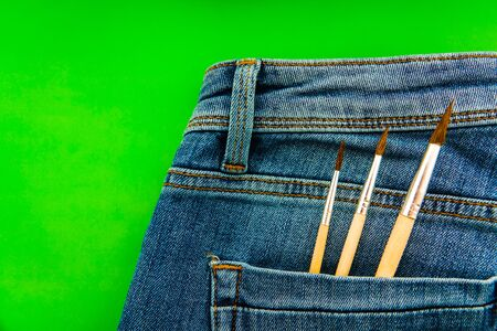 Brushes in the back pocket of blue women's jeans. Concept of a woman artist, designer, creativity, DIY, handmade 스톡 콘텐츠