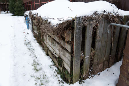 Very large three section wooden compost box standing garden in winter at countryside