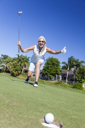 Happy successful senior woman playing golf putting a golf ball into a hole on a green and celebrating her success photo