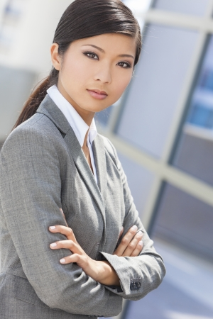 Outdoor portrait of a beautiful young Asian Chinese woman or businesswoman in smart business suit Stock Photo - 19360143