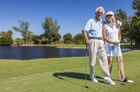 幸せな年上の男と女カップル一緒にコースでゴルフのプレーは湖に近い 写真素材