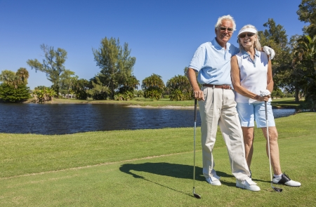 Happy senior man and woman couple together playing golf on a course near a lake
