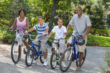 family and health: A young African American family, woman, man, father, mother & twosons  boy children riding bicycles in the summer Stock Photo