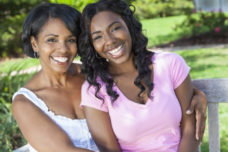 A beautiful happy middle aged African American woman mother and her daughter girl child relaxing and smiling outside together photo