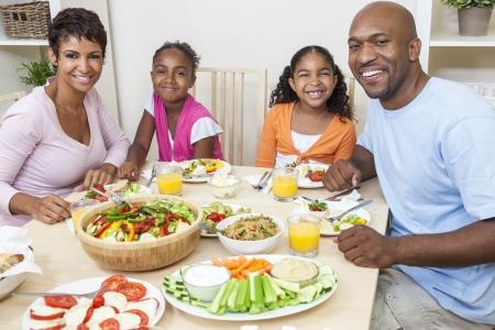 dieta sana: Un atractivo feliz afroamericano, sonriendo familia de la madre, padre, dos hijas comen ensaladas y alimentos saludables en una mesa de comedor.