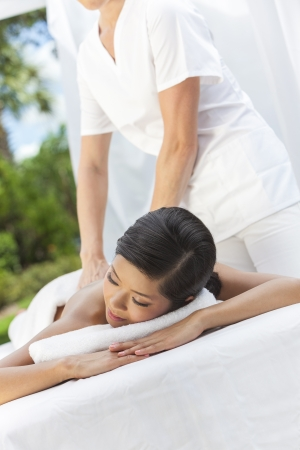 therapists: An Asian Chinese woman relaxing outside at a health spa while having a massage treatment Stock Photo