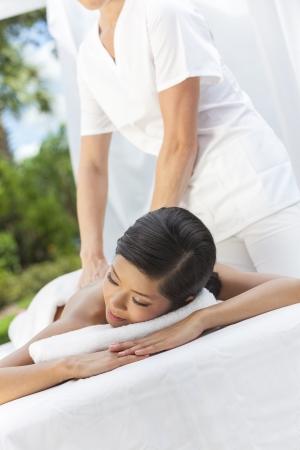 mujer china: Una mujer china asi�tica que se relaja afuera en un spa de salud aunque tengan un tratamiento de masaje