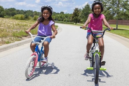 Two pretty young African American girls with a big smiles riding bicycles outside Stock Photo - 19407141
