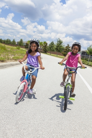 Two pretty young African American girls with a big smiles riding bicycles outside photo