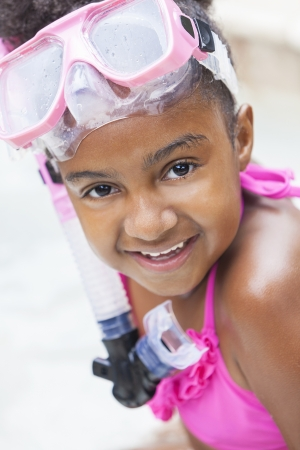 A cute happy young African American girl child relaxing on the side of a swimming pool smiling & wearing pink goggles photo