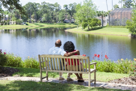 Rear view of a happy romantic senior African American couple sitting on a park bench embracing looking at a lake photo