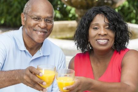 Een vrolijke, lachende man en vrouw senior Afro-Amerikaanse paar buiten het drinken van sinaasappelsap