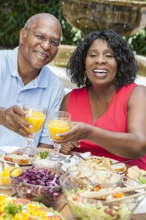 pareja saludable: Un, hombre sonriente y feliz mujer senior pareja estadounidense comer alimentos saludables en una mesa de picnic al aire libre