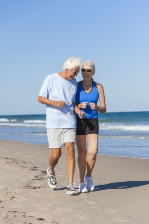 Happy senior man and woman couple together running or jogging by sea on a deserted tropical beach with bright clear blue sky
