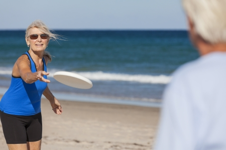 Fit and healthy senior man & woman couple playing with flying plate on a deserted beach by the sea photo
