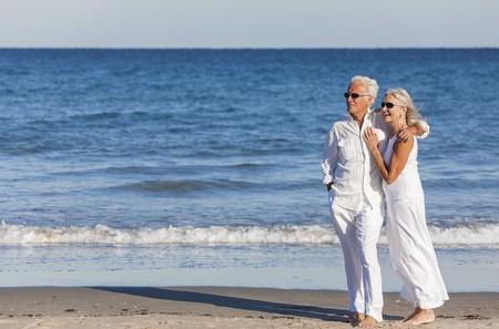 Gelukkig senior man en vrouw paar samen omarmen door zee op een verlaten tropisch strand met helder blauwe hemel