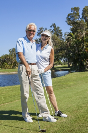 playing golf: Happy senior man and woman couple together playing golf on a course near a lake