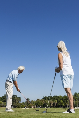 Happy senior man and woman couple together playing golf on a course near a lake they are at the tee driving down the fairway photo