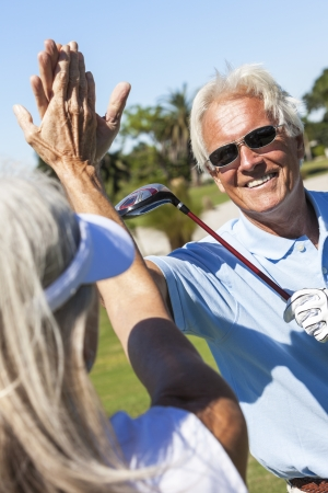 woman golf: Happy senior man and woman couple together playing golf and celebrating a good shot on the course