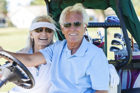 Happy senior man and woman couple together playing golf driving the golf cart or buggy on the course Banco de Imagens