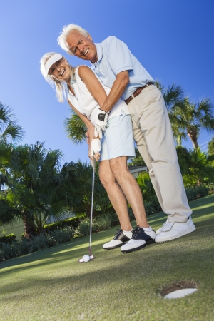woman golf: Happy senior man and woman couple together playing golf and putting on a green, the man is teaching the woman how to put.