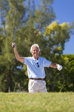 Happy successful senior man playing golf on a course Stock Photo - 19407150