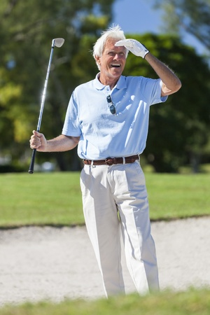 Happy senior man playing golf in a sand trap or bunker on a golf course looking at his successful shot Stock Photo - 19407093