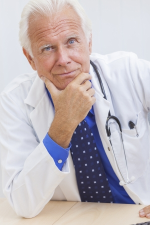 A senior male doctor sitting at a desk in an office with a computer, wearing a shirt, tie and stethoscope photo