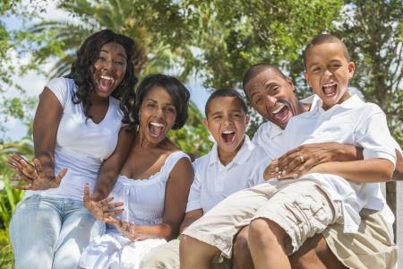 Een gelukkige zwarte Afro-Amerikaanse familie van twee ouders en drie kinderen, twee jongens een meisje, samen buiten zitten lachen plezier maken. Stockfoto