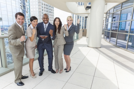Interracial business team, men & women, businessmen & businesswomen, using tablet computer or iPad and celebrating successs on a city rooftop Stock Photo - 19407143