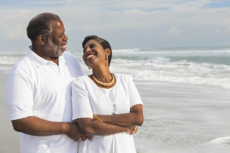 retired: Happy romantic senior African American man and woman couple on a deserted tropical beach