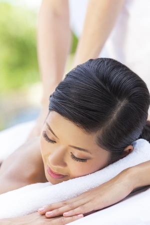 sensual massage: An Asian Chinese woman relaxing outside at a health spa while having a massage treatment Stock Photo