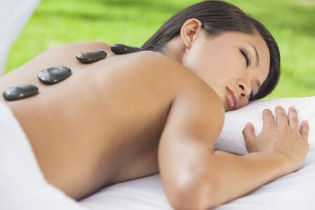 chinese woman: An Asian Chinese woman relaxing outside at a health spa while having a hot stone treatment or massage Stock Photo