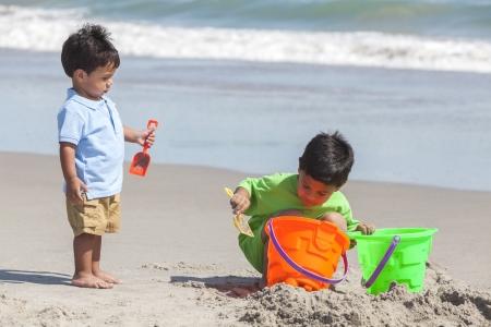 Twee gelukkige jonge Spaanse broers spelen samen op een zonnig tropisch strand met emmers en schoppen maken zandkastelen