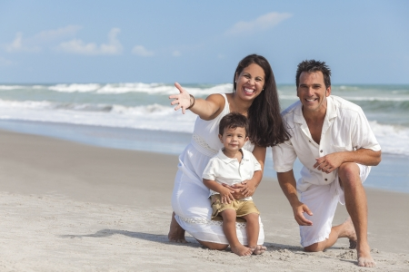 latin family: A happy family of mother, father and boy child son, playing and having fun in the sand of a sunny beach. Stock Photo