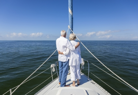 A happy senior couple embracing at the front or bow of a sail boat on a calm blue sea looking to an clear horizon Banco de Imagens