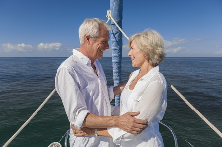 A happy senior couple embracing at the front or bow of a sail boat on a calm blue sea looking to a clear horizon