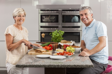 Man & woman couple preparing fresh healthy sandwiches in home kitchen with ham, cheese, salad lettuce and tomatoes photo